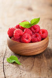 Fresh raspberries in bowl over wooden background Stock Images