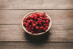 Fresh raspberries in a bowl. Ripe fresh raspberries in a bowl on wooden background Stock Images