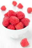 Fresh raspberries in a bowl, vertical close-up. Fresh raspberries in a bowl on a white table, vertical close-up Stock Images