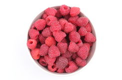 Fresh raspberries with a bowl on a white background Stock Images