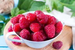 Fresh raspberries in a bowl on a wooden background. Fresh raspberries in a bowl on a wooden table Royalty Free Stock Photo