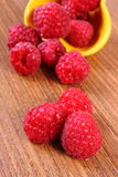 Fresh raspberries in bowl on wooden surface, healthy food Royalty Free Stock Photos