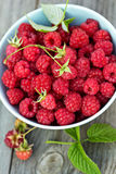 Fresh raspberries in a bowl. On a wooden table Royalty Free Stock Image
