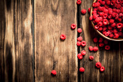 Fresh raspberries in a bowl. On a wooden table Stock Photo
