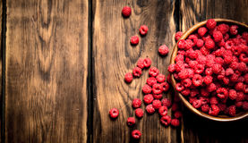Fresh raspberries in a bowl. On a wooden table Royalty Free Stock Photography