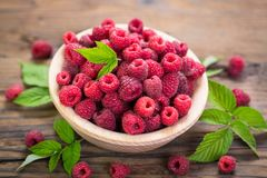 Fresh raspberries in the bowl. On the wooden table stock photos