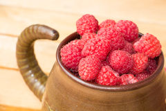 Fresh raspberries in bowl on wooden table. Fresh sweet raspberries in bowl on wooden table, summer raspberries, summer colors Royalty Free Stock Photography