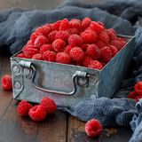 Fresh raspberries in a box. Fresh raspberries in a metal box on a wooden table Stock Photography