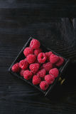 Fresh raspberries in box. Fresh organic wet ripe raspberries in black wood box over wooden burnt background. Top view with space Stock Photo