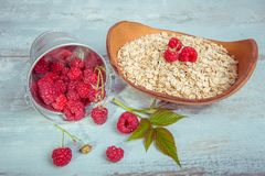Fresh raspberries in a bucket and oat flakes in a wooden bowl on a rustic wooden background. Healthy diet, vegetarian. Concept Royalty Free Stock Images