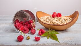 Fresh raspberries in a bucket and oat flakes in a wooden bowl on a rustic wooden background. Healthy diet, vegetarian. Concept Stock Photography