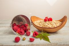 Fresh raspberries in a bucket and oat flakes in a wooden bowl on a rustic wooden background. Healthy diet, vegetarian. Concept Stock Image