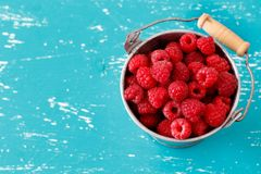 Fresh raspberries in a bucket. Fresh raspberries in a small metal bucket on a blue turquoise  background Stock Photo