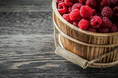 Fresh raspberries in bucket on vintage wooden board.  Royalty Free Stock Photos