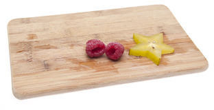 Fresh Raspberries and Carambola Starfruit. On a Cutting Board. Isolated on white with a clipping path Stock Photos