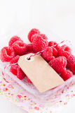 Fresh raspberries and cardboard tag. Closeup of fresh red raspberries in plastic container with cardboard tag resting on floral serviette on light surface Royalty Free Stock Photos