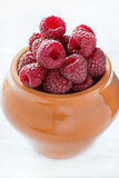 Fresh raspberries in ceramic pot. Selective focus Royalty Free Stock Photos