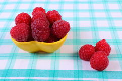 Fresh raspberries on checkered tablecloth, healthy food. Fresh raspberries on checkered tablecloth, concept of healthy food and dessert Royalty Free Stock Photo