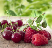 Fresh raspberries and cherries. Macro shot of fruit on the wooden table Royalty Free Stock Photography