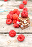 Fresh raspberries with chocolate cubes. Fresh raspberries with ice chocolate and flowers forget-me-on the old wooden table outdoorsselective focus Stock Photo