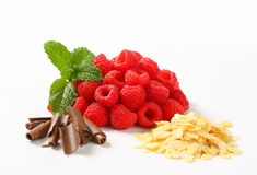 Fresh raspberries, chocolate curls and sliced almonds. Heaps of fresh raspberries, chocolate curls and sliced almonds Royalty Free Stock Photography