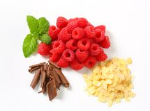 Fresh raspberries, chocolate curls and sliced almonds. Heaps of fresh raspberries, chocolate curls and sliced almonds Royalty Free Stock Images