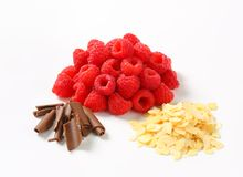 Fresh raspberries, chocolate curls and sliced almonds. Heaps of fresh raspberries, chocolate curls and sliced almonds Royalty Free Stock Image
