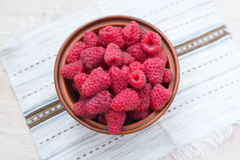 Fresh raspberries. Clay bowl with fresh raspberries on a light background Stock Image