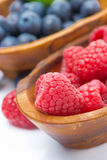 Fresh raspberries close-up and blueberries in a wooden bowls. Vertical Stock Photos