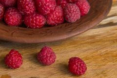 Fresh raspberries close up. Fresh raspberries on a wooden background, closeup Royalty Free Stock Photo