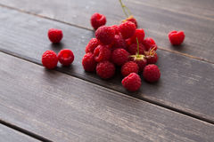 Fresh raspberries closeup on wood background. Fresh raspberries on wood background. Bowl with natural ripe organic berries closeup on wooden table Stock Images