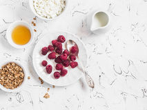 Fresh raspberries, cottage cheese, granola, honey and cream - delicious Breakfast. On a light background. Top view Royalty Free Stock Photography