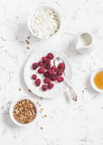 Fresh raspberries, cottage cheese, granola, honey and cream - delicious Breakfast. On a light background, top view Royalty Free Stock Photography
