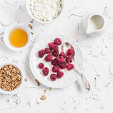 Fresh raspberries, cottage cheese, granola, honey and cream - delicious Breakfast. On a light background. Top view Stock Photo
