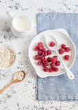 Fresh raspberries, cream and oats on a light background, top view. Delicious breakfast or snack Stock Photography