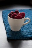 Fresh raspberries in cup. Closeup of fresh raspberries in white cup on a blue mat with shaddow background Royalty Free Stock Photo