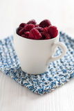 Fresh raspberries in cup. Closeup of fresh raspberries in white cup on a blue mat Stock Photo