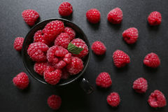 Fresh raspberries in a cup on black background. Closeup of fresh raspberries in a cup on black background Royalty Free Stock Images