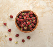 Fresh raspberries with a fruit stem. In a wooden dish on a marble background - top view Stock Photography