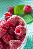 Fresh raspberries in glass bowl. With leaf and turquoise pad Stock Image