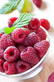 Fresh raspberries in glass bowl. With leaf Royalty Free Stock Photography