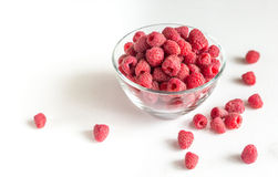 Fresh raspberries in the glass bowl. On the white background Royalty Free Stock Photo