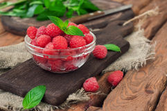 Fresh raspberries. In a glass bowl on a wooden table. Copy space. A eye level Closeup Royalty Free Stock Photos