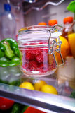 Fresh raspberries in a glass jar on a shelf open refrigerator Stock Image