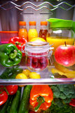 Fresh raspberries in a glass jar on a shelf open refrigerator Royalty Free Stock Photo