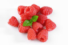 Fresh raspberries. Handful of fresh raspberries with leaves on white background Royalty Free Stock Images