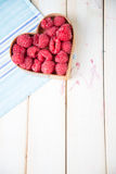 Fresh raspberries in heart shape basket on kitchen. Fresh organic raspberries in heart style shape basket  on white background retro kitchen table and blue Royalty Free Stock Photo
