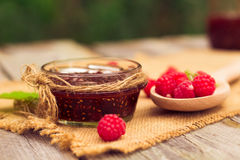 Fresh raspberries and jam on wooden table. Selective focus Stock Image