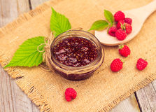 Fresh raspberries and jam on wooden table. Selective focus Stock Images