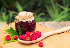Fresh raspberries and jam on wooden table. Selective focus Royalty Free Stock Image